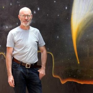 A man standing in front of a mural showing a comet.