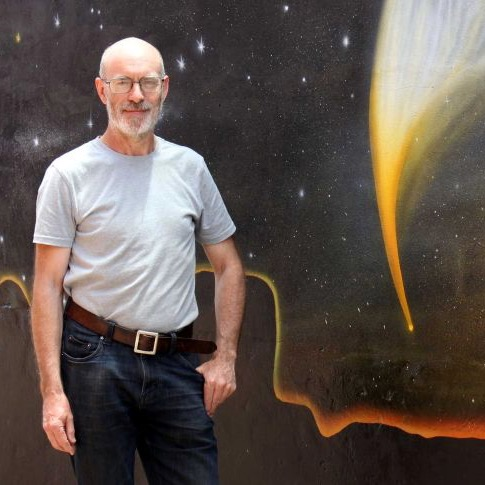 A bald, bearded man in a t-shirt, standing in front of a mural showing a comet.
