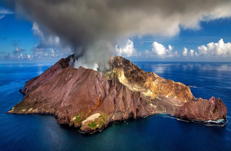 Blue sea around steep, rocky island with smoke boiling up from a central crater at the top.