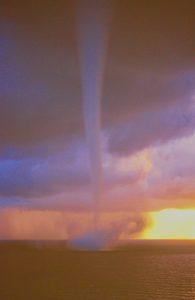Waterspout set against a bright golden sunrise sky.