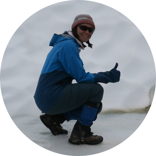 Smiling woman in arctic gear, crouched on ice, giving a thumbs-up.