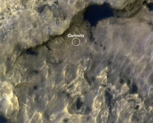 Dark spot with white ring around it and white text, on reddish rocky terrain seen from above.