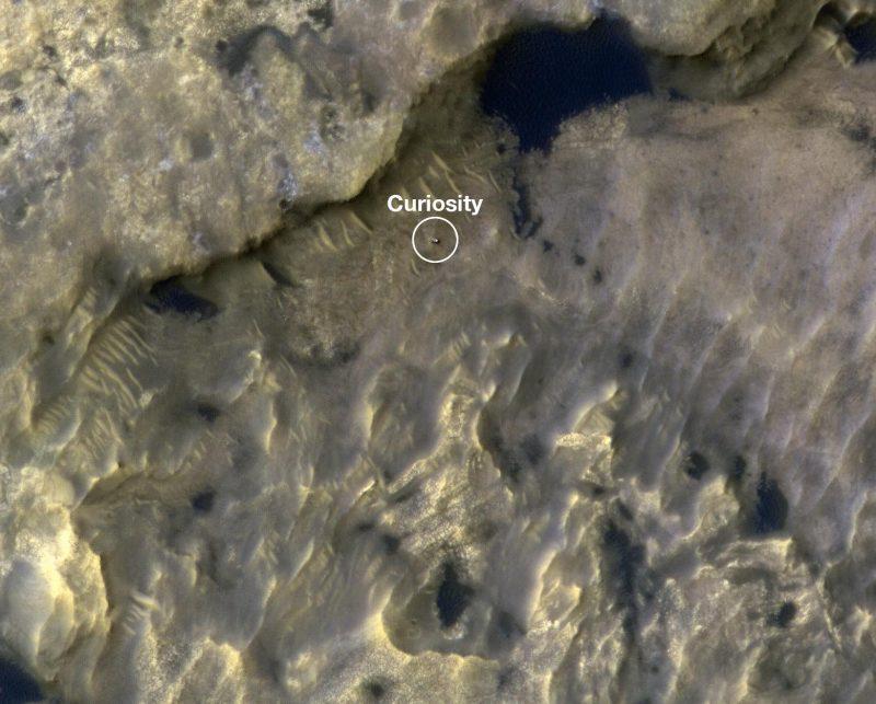 Ponto minúsculo, escuro, quadrado com anel branco à sua volta e texto branco, em terreno rochoso irregular visto de cima.