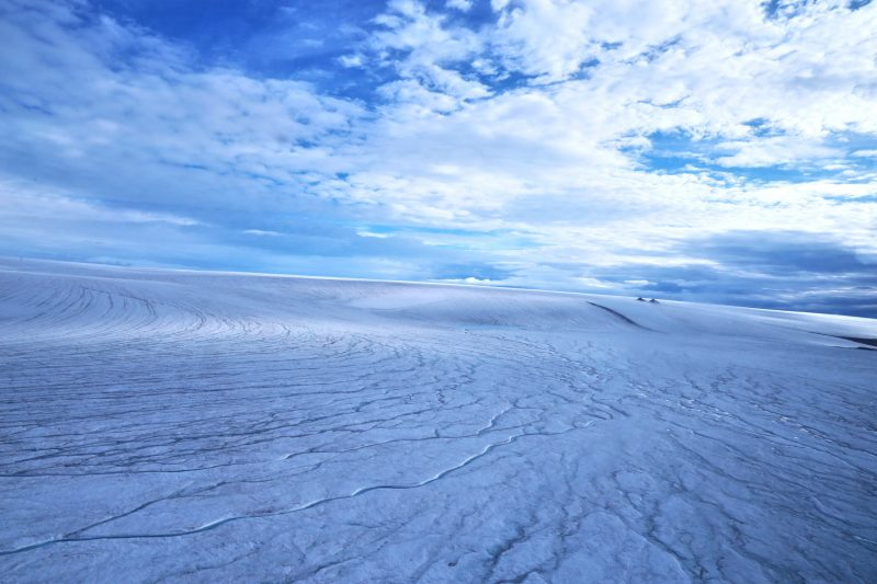 Icy landscape with blue sky and clouds above.