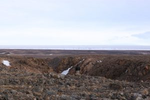 Man standing on rocky terrain looking at ice terrain in the distance, with overcast sky.
