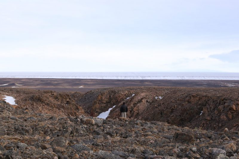 Inconspicuous man standing on rocky terrain looking at ice terrain in the distance, with overcast sky.