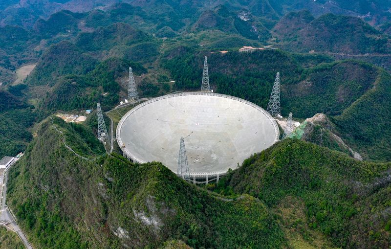 Large radio telescope dish with five towers around it, surrounded by forest.