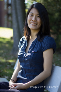 Smiling woman sitting on bench with tree in background.