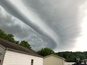Long, curved, bar-like linear cloud over buildings.