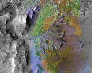 Colorful overhead view ofd rocky terrain with river channel and delta.