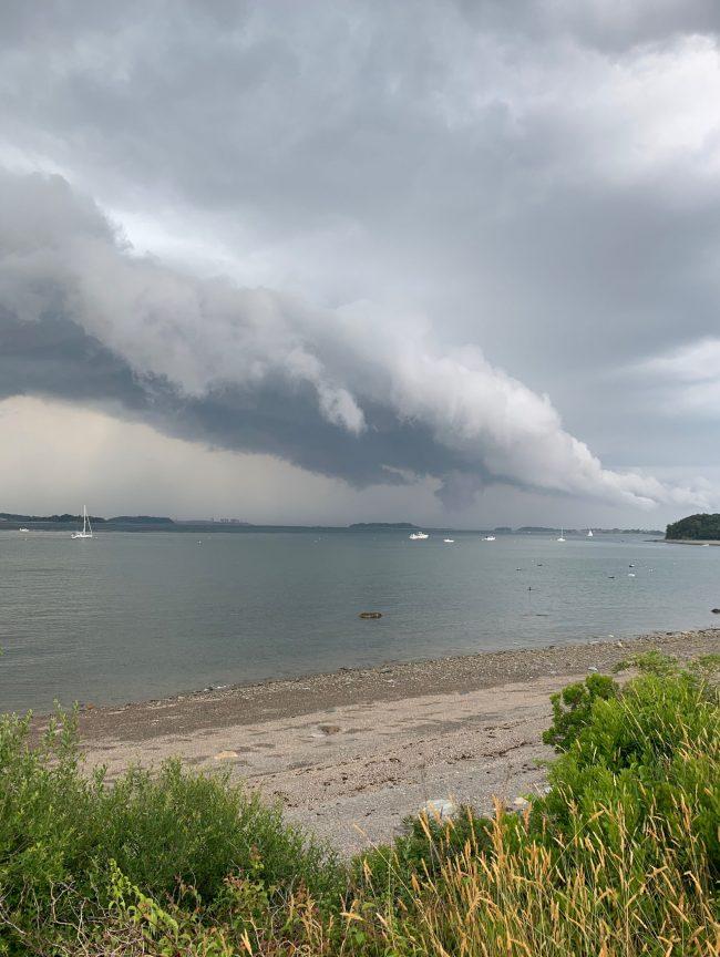 Long, flat linear cloud over gray water.