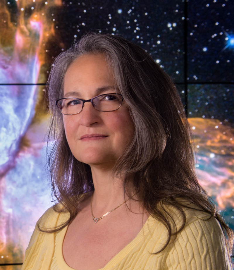 Woman with long hair, glasses and yellow blouse, with nebula mural in background.
