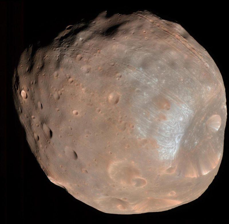 Lua rochosa avermelhada e oblonga sobre fundo preto.