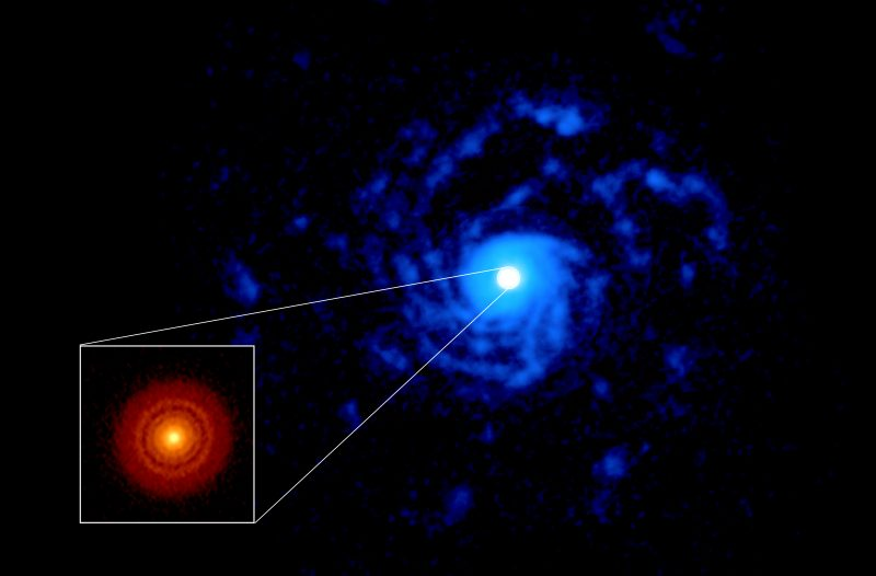 Large blue spiral with white center and a smaller reddish disk in an outlined square inset, on black background.