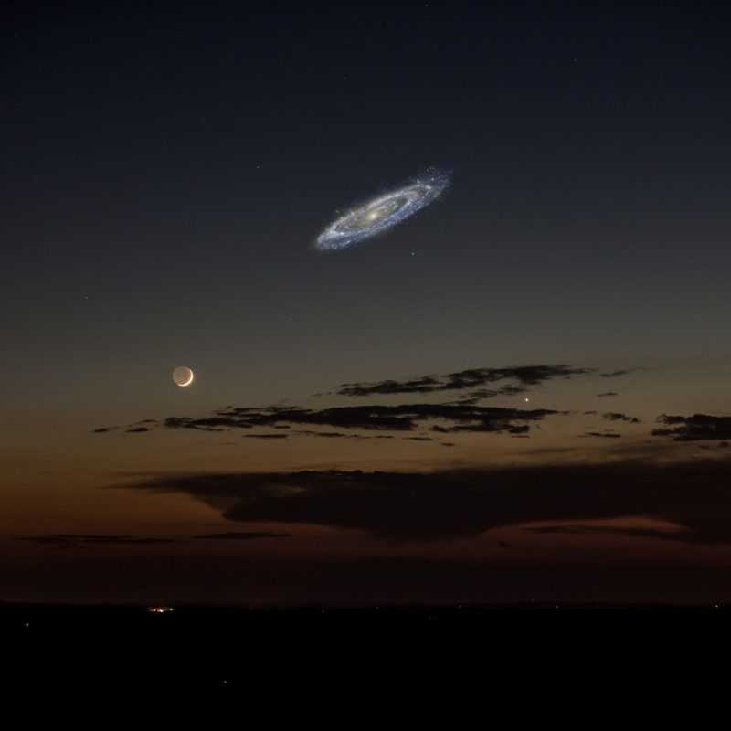 A very bright Andromeda galaxy hanging in the sky, several times the size of a crescent moon.