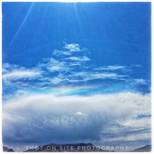 Circumhorizon arc over a ridgeline, with the sun just out of view at the top of the image.