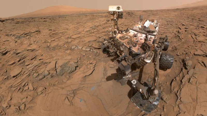 Dusty 6-wheeled rover looking our way with a camera on a pole, in reddish Martian desert.