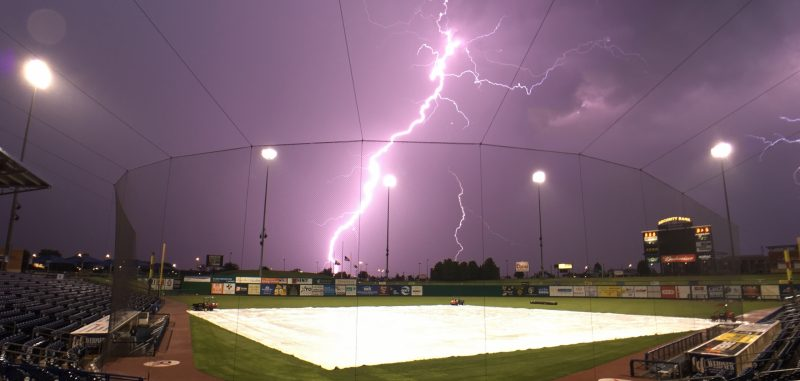 Huge bolt of lighting in a purple sky over a baseball diamond.