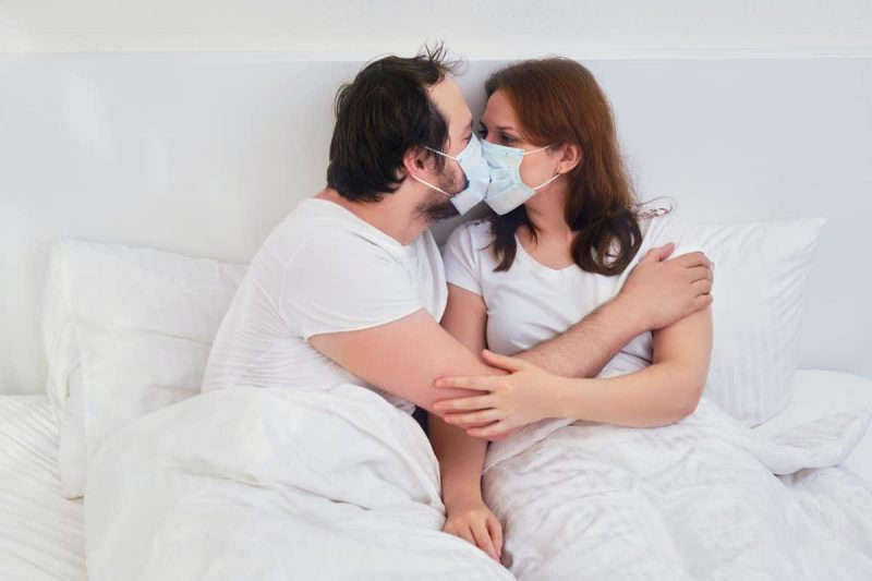 Man and woman kissing in bed wearing masks.