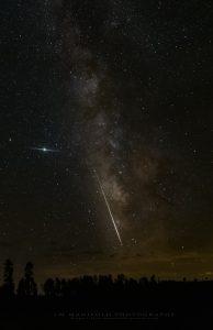 Bright meteor streaking along Milky Way.