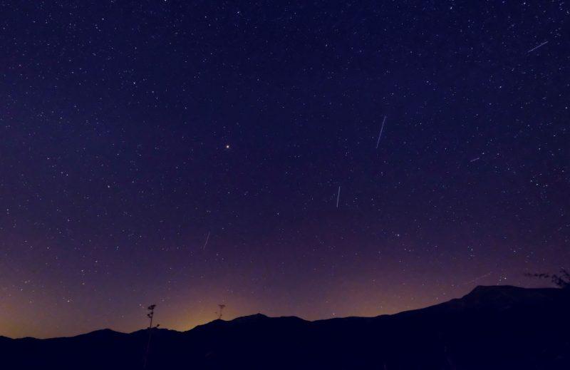 Several short white streaks in a dark sky.