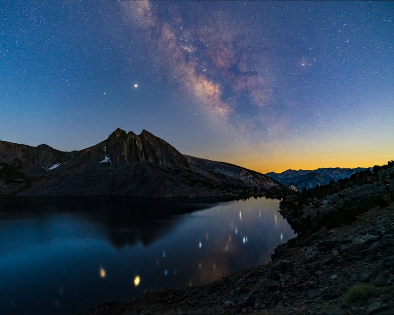 Milky Way and bright planets hanging in the sky above a mountain, and reflected in a lake.