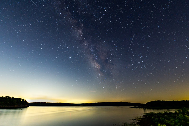 Edgewise view of the summer Milky Way, on a starry night with light near the horizon and thin streaks in the sky.