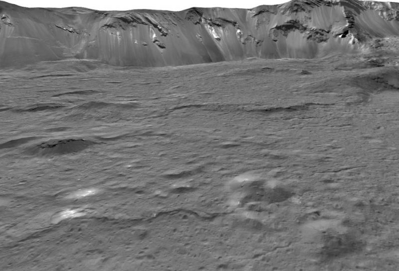 A somewhat lumpy crater floor with steep crater wall in distance.