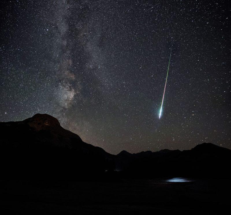 Over dark hills, Milky Way and bright streak much brighter toward lower end.