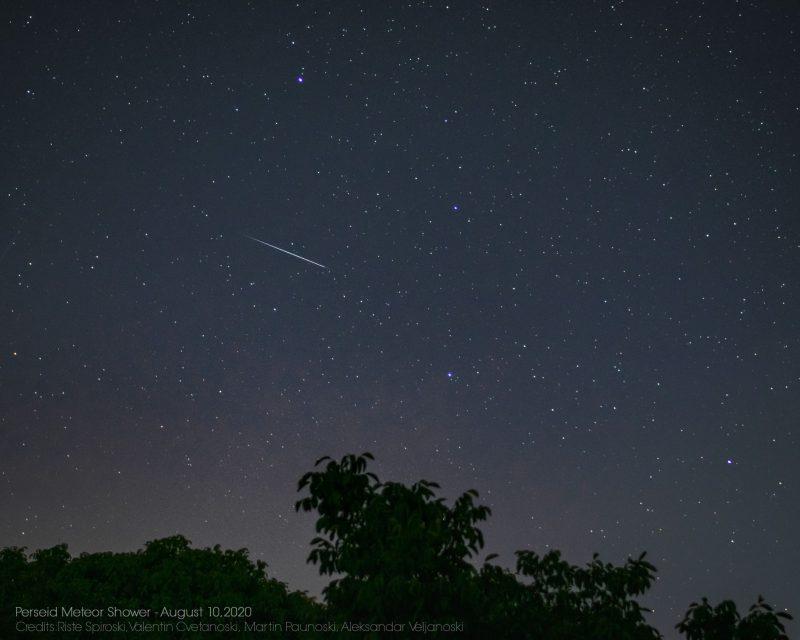 Starry black sky with thin white streak in upper left.