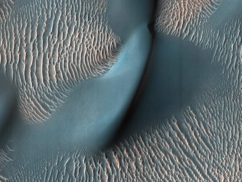 Lisa colina - uma duna - rodeada por muitas ondulações paralelas muito pequenas e estreitas.