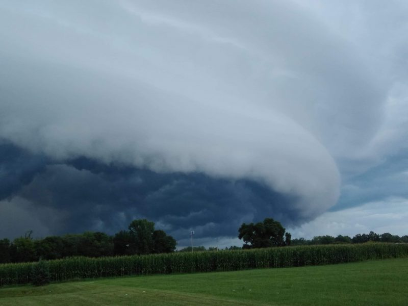 A dark, bulging, flat cloud moving over a green pasture.
