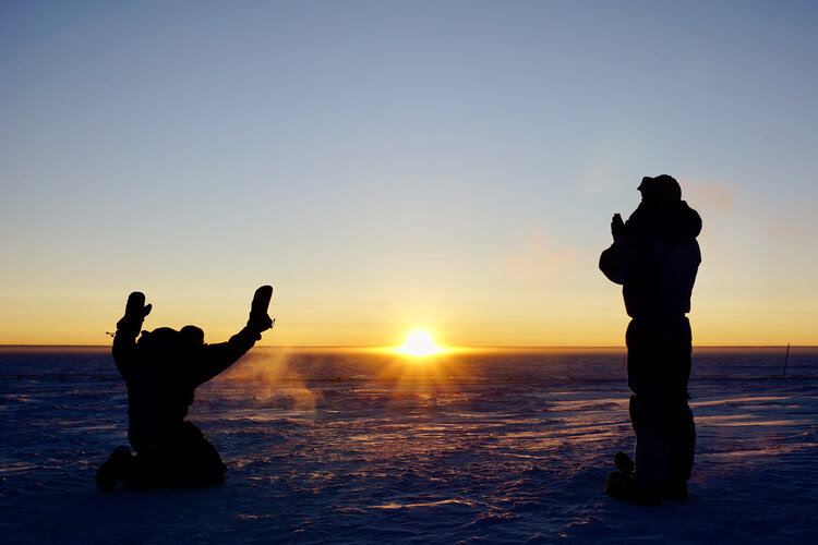 Sunrise over a frozen landscape, with 2 silhouetted researchers in Arctic garb looking on reverently.