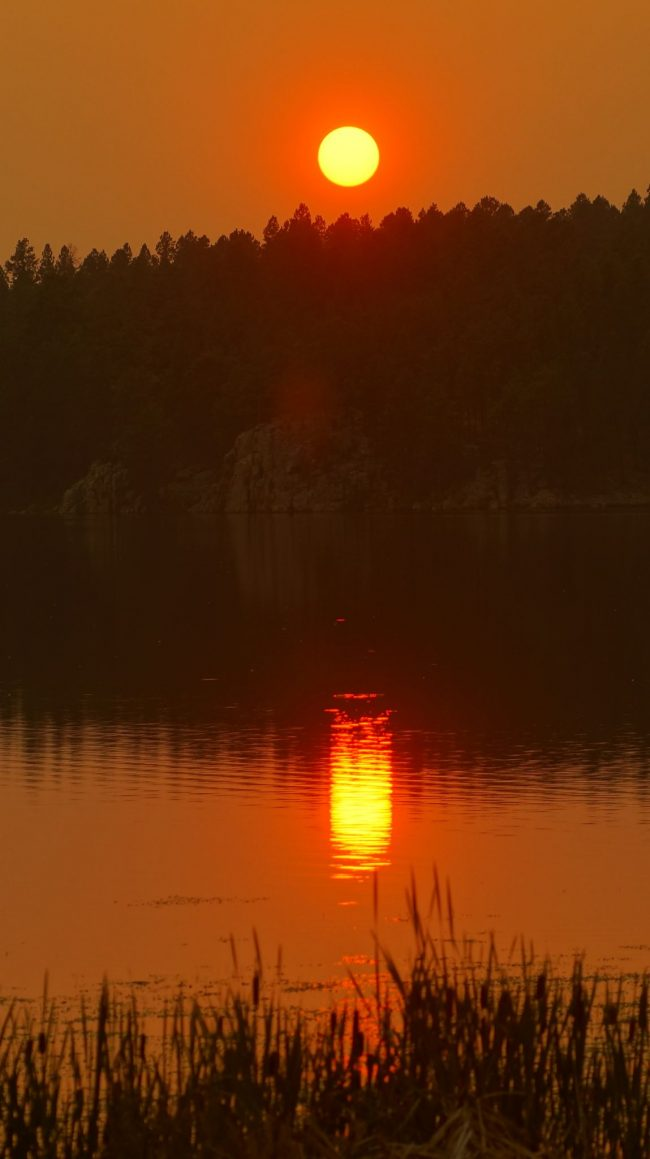 Orange wildfire sunset in the sky, and also reflected in a lake.