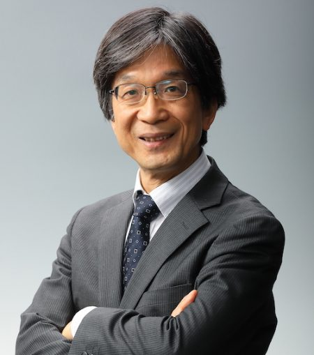 A smiling and dapper Japanese man, with glasses, wearing a suit.