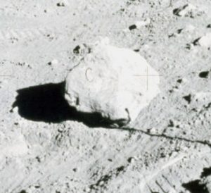 """A rock sits on the lunar surface with a marking that resembles the letter """"C."""""""