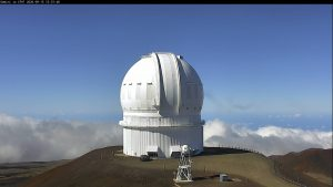 Telescope dome on top of mountain with clouds and blue sky in background.