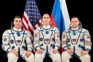 Three seated astronauts, in flight suits.