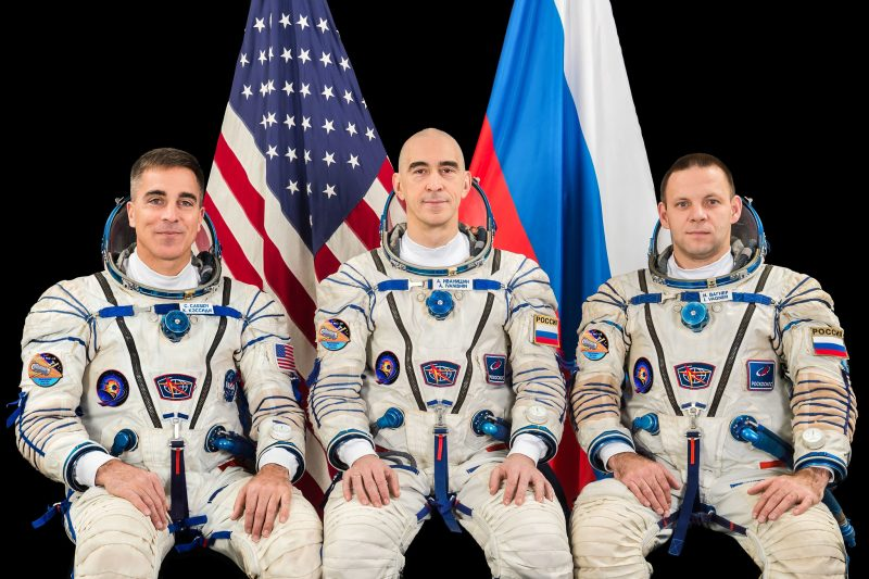 Three seated astronauts, in flight suits, with American and Russian flags behind them.