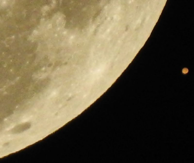 Small orange-red dot next to slice of the moon with craters and gray blotches.