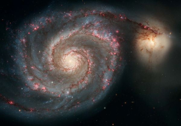 Galaxy with spiral arms full of stars and pink blotches, and smaller golden galaxy beside it.