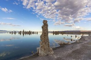 Lake with tall pillars around shoreline and blue sky with clouds.