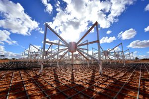 Large spider-like artificial structures in field, with blue sky and puffy clouds.