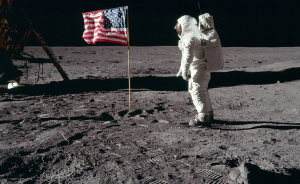 """Apollo astronaut Buzz Aldrin is saluting the American flag as a ripple goes through its center, appeared to be caused by """"wind."""""""