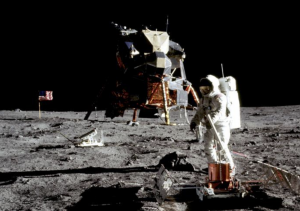An Apollo astronaut stands in front of the Eagle lander as a starless, black sky is seen behind them.