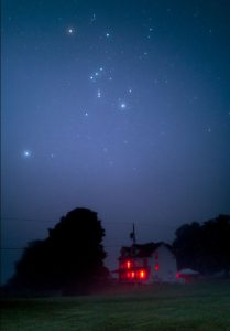 Orion and Sirius in misty blue sky above old two-story farmhouse with lighted windows.
