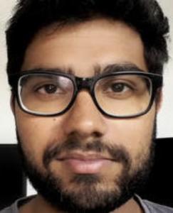 A young, intelligent looking man: glasses, dark hair, beard eyes.