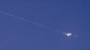 """A fiery meteor flashing across a daylight sky; it looks like space junk in that different materials in the object are """"popping"""" or exploding via vaporization, as it falls."""