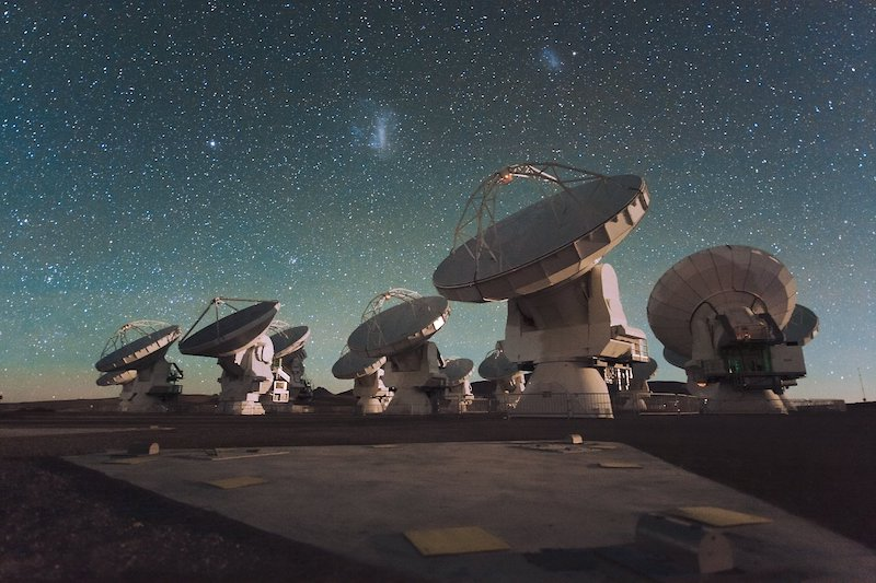 Seven huge dish-shaped antennas on bases under a starry sky.