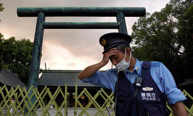 A man in police cap and vest, with tall Japanese structure in background.